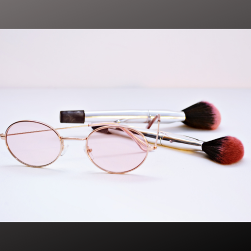 Pink Womens Glasses Next To Makeup Brushes